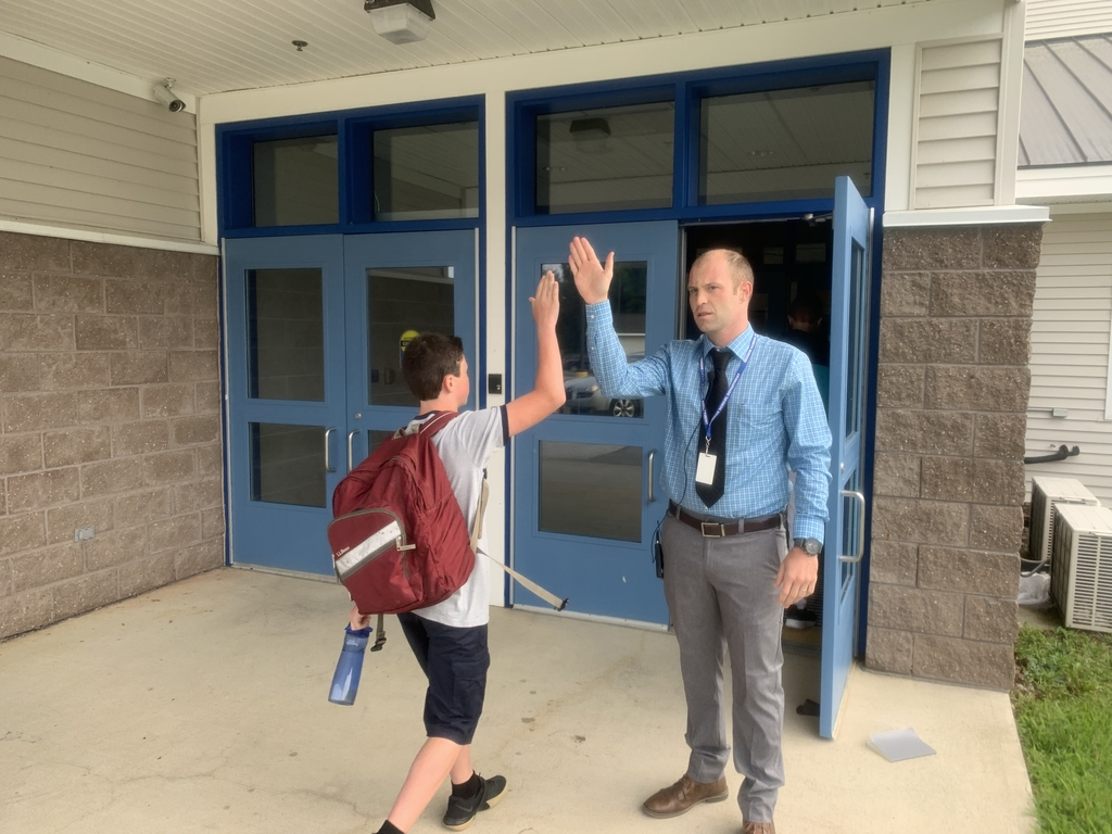 Principal Grant greets HMS students with a high 5!